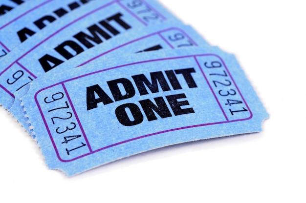 Varios boletos azules de la admisión en un fondo del libro blanco.