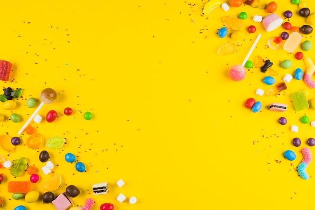 Varios caramelos de colores y piruletas en superficie amarilla