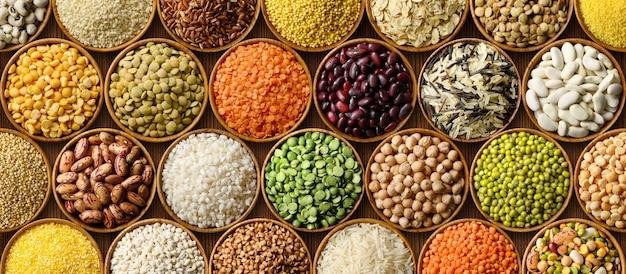 Varios cereales secos y legumbres de fondo, arroz, lentejas, frijoles, mijo, alforfón, garbanzo en cuencos de madera vista superior