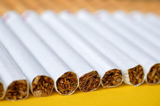 Varios cigarrillos clásicos yacen en ángulo en amarillo