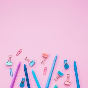 Varios clips de papel y crayones de colores sobre fondo liso