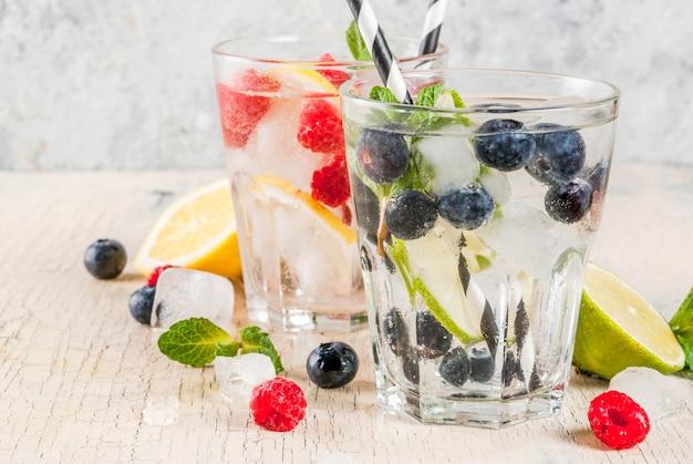 Varios cócteles de limonada de bayas o mojito, agua fresca infundida de lima limón, frambuesa, arándano