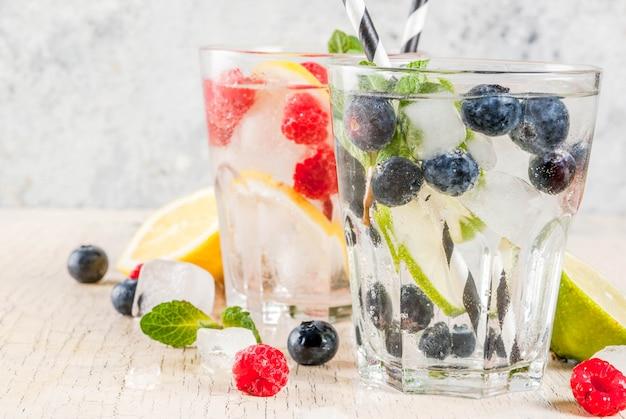 Varios cócteles de limonada de bayas o mojito, agua fresca con limón, lima, frambuesa, arándano, agua infundida