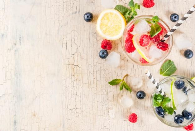 Varios cócteles de limonada o mojito de bayas, agua fresca infundida de limón, lima, frambuesa, arándano, agua infundida, bebidas de desintoxicación saludables de verano, espacio de copia de fondo claro arriba
