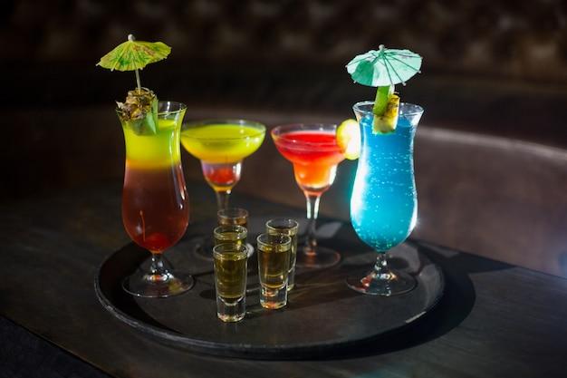 Varios cócteles y vasos de tequila en la bandeja de servir