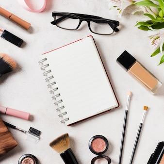 Varios cosméticos y gafas esparcidas alrededor de cuaderno en blanco