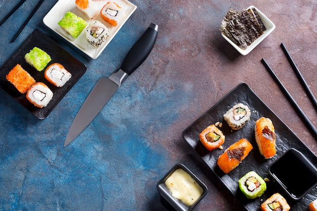 Varios deliciosos sushi y rollos en pizarra, salsa sobre fondo de piedra oscura