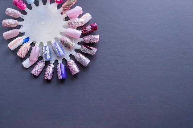 Varios diseños de uñas pintados a mano aislados en gris. gran variedad de esmaltes de uñas en diferentes colores. manicura artística. esmalte de uñas. salón de belleza copyspace