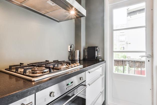 Varios electrodomésticos de cocina modernos en mostradores ubicados cerca de la puerta del balcón cerrada en el apartamento de luz