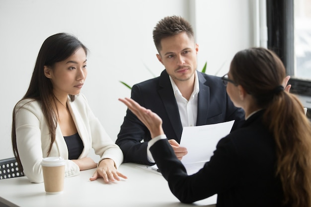 Varios escépticos gerentes de recursos humanos entrevistando a una candidata, mala primera impresión