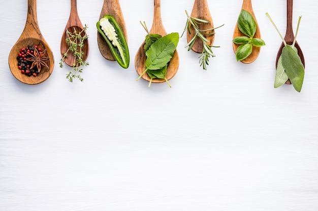 Varios de especias y hierbas en cucharas de madera.