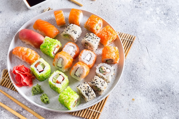 Varios frescos y deliciosos juegos de sushi en pizarra blanca con palos de madera, salsa sobre fondo de piedra clara
