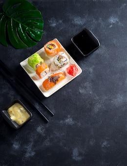 Varios frescos y deliciosos juegos de sushi en pizarra negra con palitos de pizarra, salsa sobre fondo de piedra negro