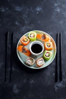 Varios frescos y deliciosos juegos de sushi en placa de cerámica con palitos de pizarra, salsa sobre fondo de piedra negro