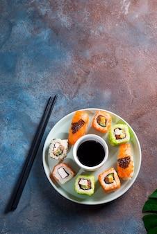 Varios frescos y deliciosos juegos de sushi en placa de cerámica con palitos de pizarra, salsa sobre fondo de piedra