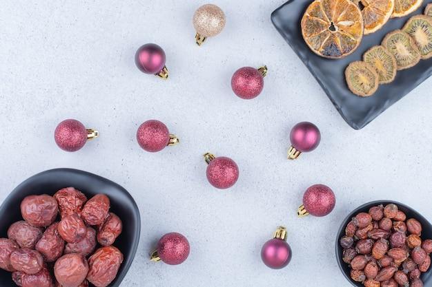 Varios frutos secos y bolas de navidad en la superficie de mármol.