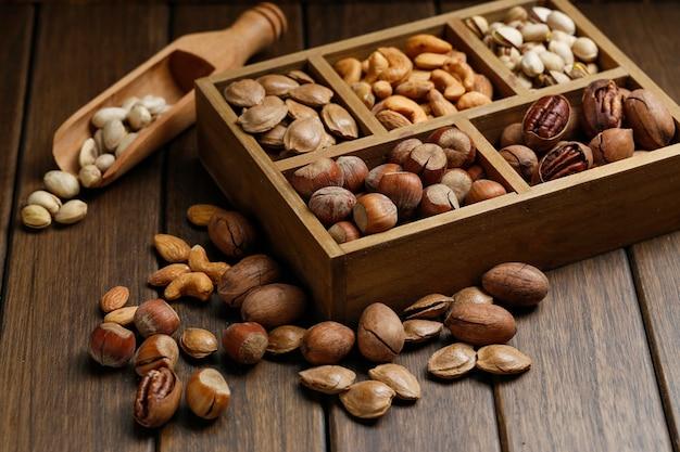 Varios frutos secos en caja de madera Foto gratis