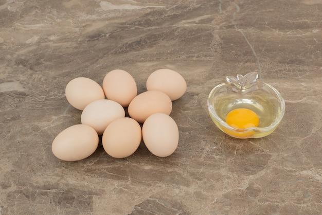 Varios huevos con huevo crudo en el plato en la superficie de mármol