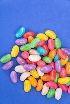 Varios jelly beans sobre fondo azul.