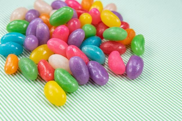 Varios jelly beans sobre fondo de rayas verdes con blanco