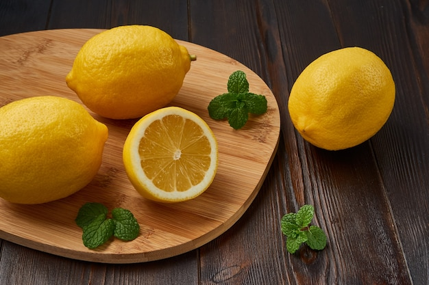 Varios jugosos limones amarillos con hojas de menta sobre una tabla para cortar