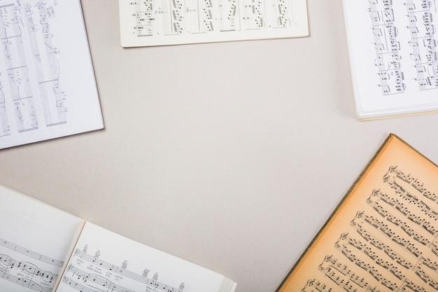 Varios libros de notas musicales sobre fondo blanco con espacio para texto