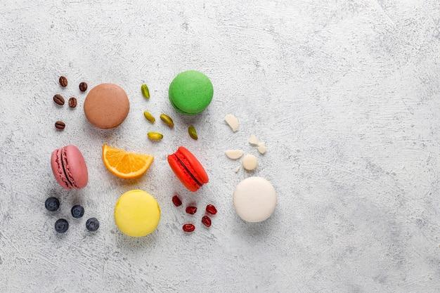 Varios macarrones con pistachos, frutas, bayas, granos de café.