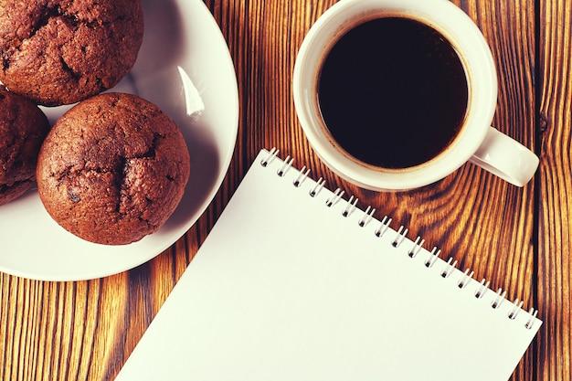 Varios muffins de masa de chocolate negro con una taza de café y un bloc de notas sobre una mesa de madera.