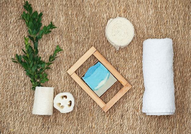 Varios objetos relacionados con el spa sobre fondo de paja, vista superior. jabón natural artesanal y complementos para el cuidado corporal.