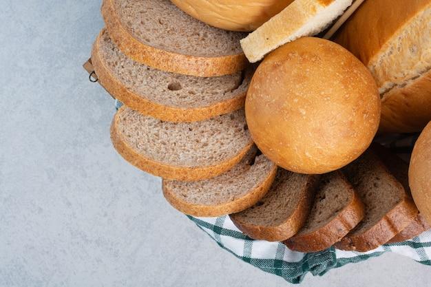Varios panes en la canasta sobre fondo de mármol. foto de alta calidad