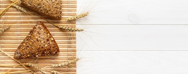 Varios panes pequeños de forma triangular de grano múltiple rociados con semillas de girasol enteras