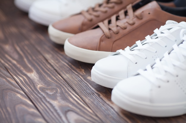 Varios pares de zapatillas coloridas colocadas en el fondo del piso de madera