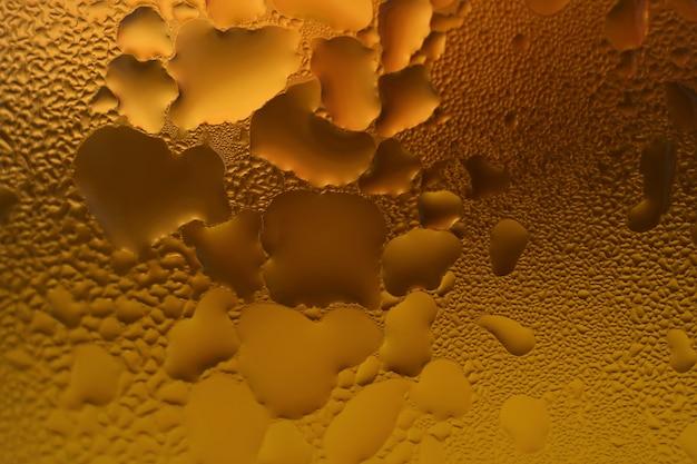 Varios patrones de condensación en el vaso lleno de cerveza helada color ámbar.