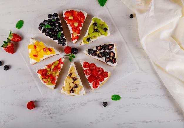 Varios pedazos de tarta hermosa con bayas frescas