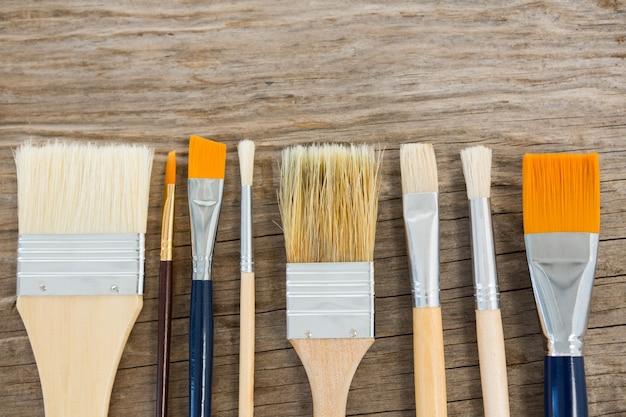 Varios pincel dispuestos en una fila sobre la superficie de madera