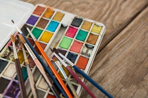 Varios pincel y paleta sobre superficie de madera