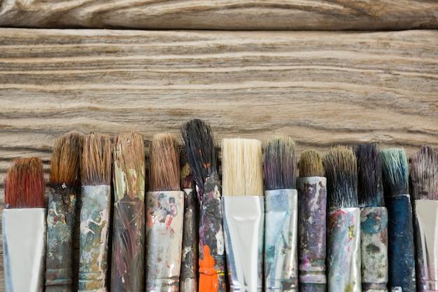Varios pincel sucio dispuestas en una fila sobre la superficie de madera