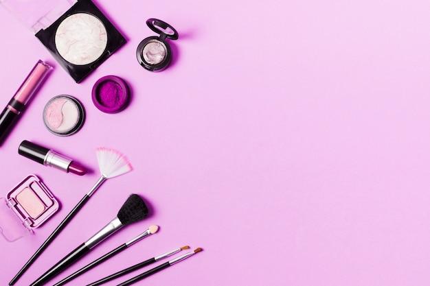 Varios pinceles y cosméticos en tinte púrpura.