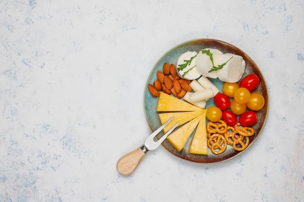 Varios platos de queso y queso en la mesa de luz con diferentes nueces y frutas