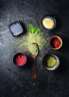Varios polvo de té matcha sobre un fondo de hormigón. cuchara de madera con polvo de té matcha esparcido con hojas.