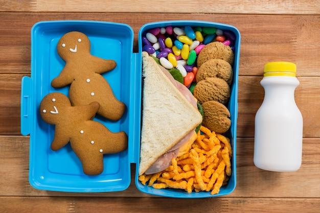 Varios productos dulces y aperitivos en la caja de almuerzo