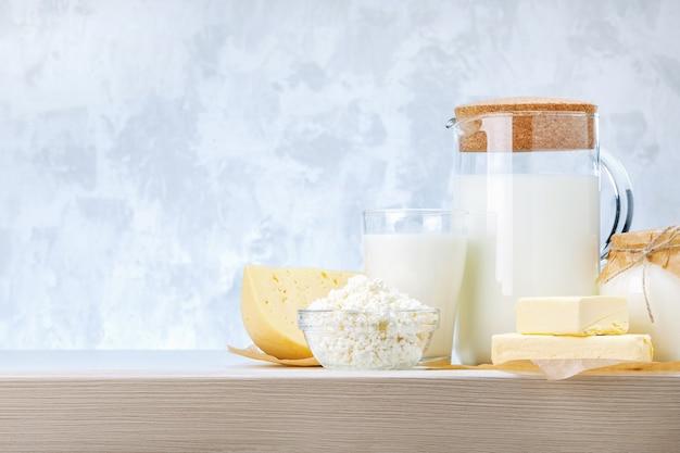 Varios productos lácteos en la mesa de madera contra un fondo gris con espacio de copia.