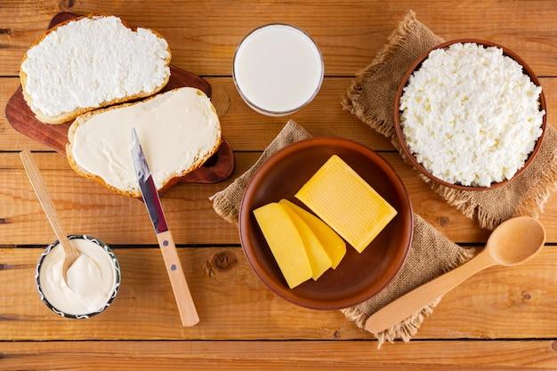 Varios productos lácteos. pan con queso crema sobre tablas de madera. vista superior