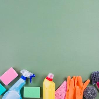 Varios productos de limpieza en la parte inferior de la superficie verde