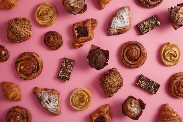 Varios productos de panadería dulces apetitosos aislados sobre fondo rosado. varios croissants, bollos en polvo con azúcar, galletas rellenas de mermelada, muffins de chocolate, deliciosos panecillos. surtido de confitería