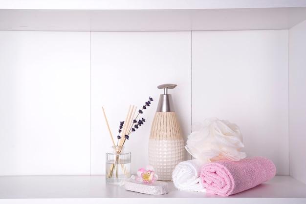 Varios productos de spa y belleza en estantería blanca.
