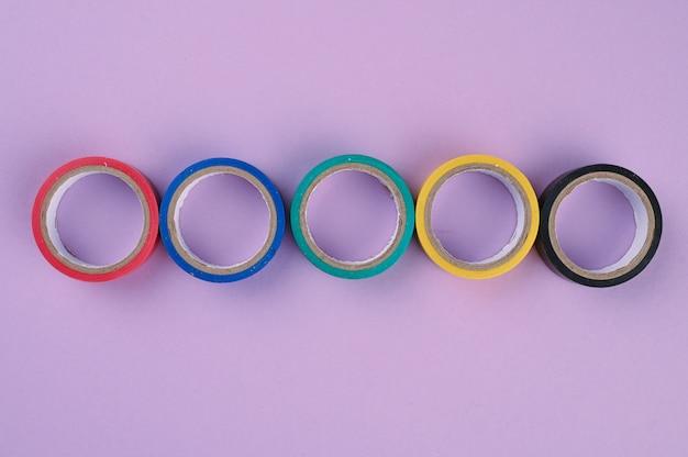 Varios rollos redondos de cinta plástica de colores se encuentran en una fila