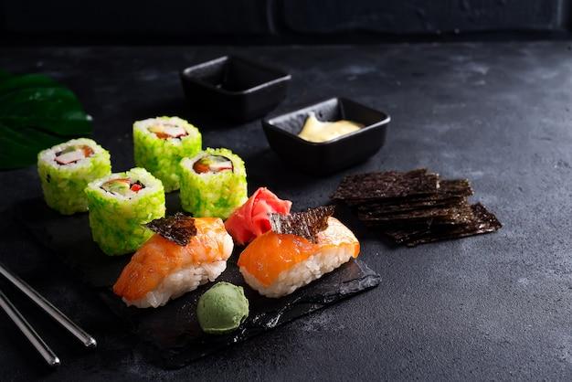 Varios sushi en pizarra negra con palitos de pizarra, salsa y nori en negro