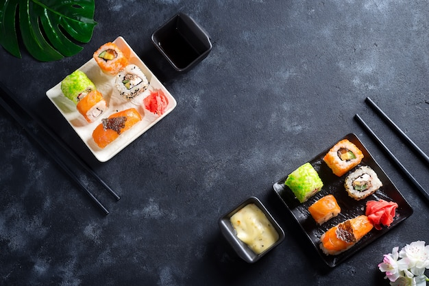 Varios sushi en pizarra con palitos de pizarra, salsa y nori sobre negro