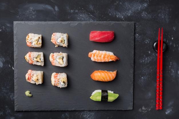 Varios sushi y rollos en placa de pizarra y mesa de piedra negra con palillos y wasabi